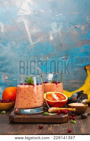 Healthy Refreshing Pink Smoothie With Apple, Red Oranges, Cowberry And Bran With Ingredients On Wood