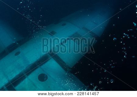 Picture Of A Wing Of A Scuttled Airplane With The Air Bubbles Coming From Divers Underneath, Aqaba,