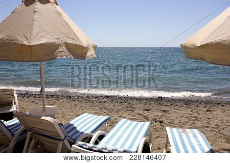 Umbrellas And Striped Sun Loungers On A Sunny Afternoon On A Sandy Beach By The Blue Sea Without Peo