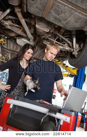 Concentrated man and woman looking at laptop while standing in garage
