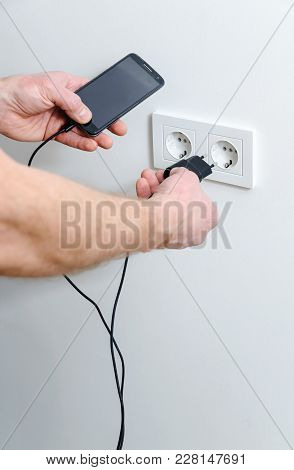 A Man Is Inserting The Plug Into The Wall Socket To Charge The Smartphone.