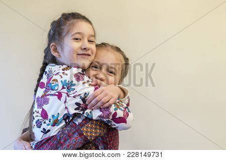 Two Little Girls Sisters Hugging. The Manifestation Of Sisters' Love And Friendship