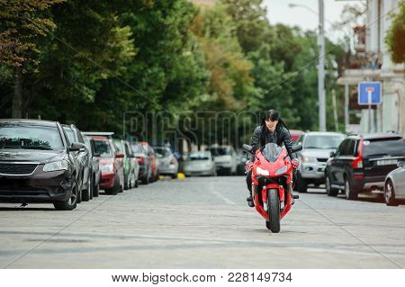 A Biker Girl In A Leather Jacket On A Motorcycle Rides In The City