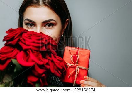 Woman With Red Gift Box And Bouquet Of Beautiful Roses On Grey, Copy Space. Valentine Day, Women Day
