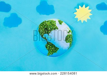 Earth Model Made Of Paper And Fresh Green Sprouts Collage On Blue Background With Paper Sun And Clou