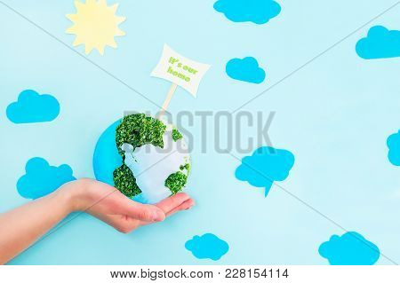 Female Hands Holding Earth Paper And Green Sprouts Collage Model With It's Our Home Pointer On Blue