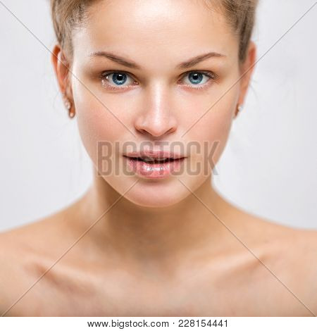 Portrait Of A Beautiful Young Smiling Woman On A Gray Background