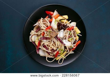 Udon Wok Noodles With Pork And Peppers, Served On Black Plate, Flat Lay. Japanese Cuisine, Restauran