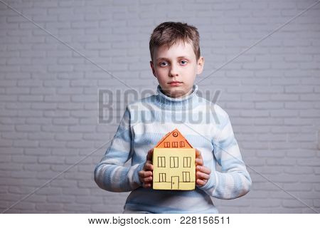 Homeless, orphan, settler, migrant, adoption concept. Boy with cardboard toy house in hands dreaming about real home poster