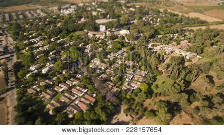 Aerial View Of Red Houses Rooftops With Green Grass And Trees In The Suburb Of Israel. Tilt Shift Bo