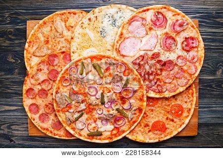 Many Pizzas With Assorted Toppings On Rustic Wooden Table, Top View. Food Background