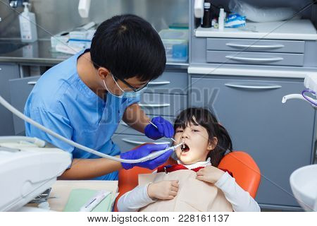Pediatric Dentistry, Prevention Dentistry Concept. Dentist Cleaning Little Asian Girl's Teeth. Oral