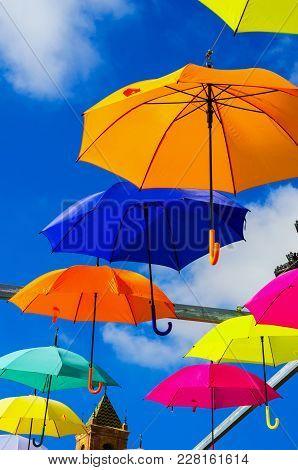 Colourful Umbrellas Urban Street Decoration. Hanging Colorful Umbrellas Over Blue Sky, Tourist Attra