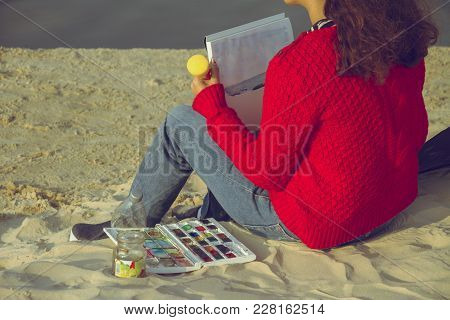 Woman In A Red Sweater Holding A Brush And Painting With Color Waters On A Sandy Beach. Set Of Color