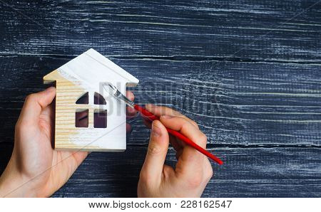 Hand Paints A House. Concept Of Repair, Hobby, Work. Repair And Painting Of Wooden House Figurines.