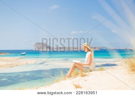 Relaxed Woman Enjoying Sun, Freedom And Good Book An Beautiful Sandy Beach Of Balos In Greece. Young
