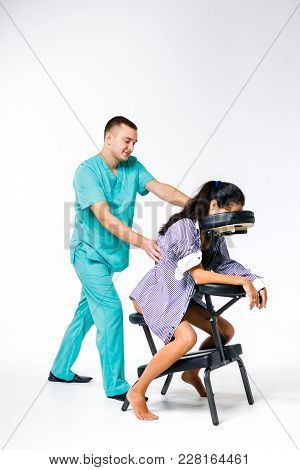 Theme Massage And Office. Male Therapist With Blue Suit Doing Back And Neck Massage For Young Woman