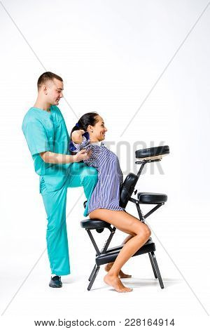 Theme Massage And Office. Young Male Therapist In Blue Suit Doing Back Massage With His Knee Braced