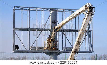Construction Site And Big Billboard. People Working Building New Big Billboard. Worker Repairing Bil