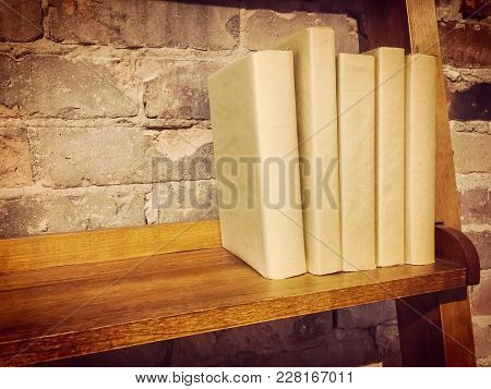 Books In Paper Covers On A Wooden Shelf, Near A Brick Wall. Retro Style Image.