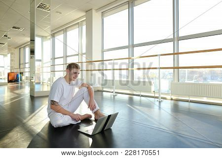Guy Dancing With Laptop Lessons At Gym Studio. Young Man Wears White Suit. Concept Of Internet Tutor