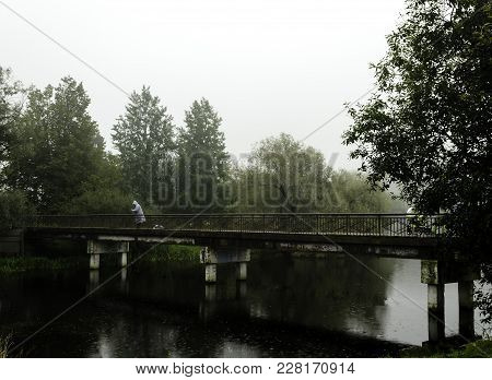 One Fisherman Catching Fish In The River On The Bridge