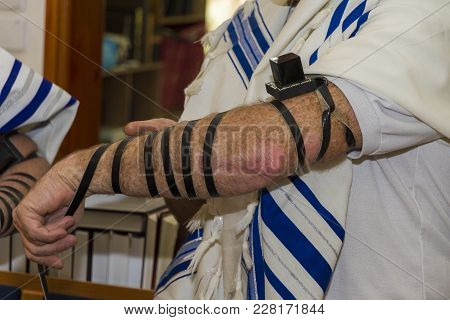 An Adult Man Putting A Jewish Tefillin On His Arm And Wearing Prayer Shawl For Praying. Preparing Fo