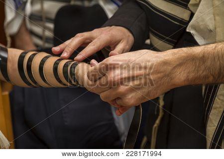 An Orthodox Man, Wearing Prayer Shawl, Put A Jewish Tefillin On A Young Man Arm Preparing For A Pray