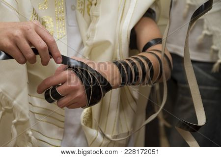An Young Man Wrapping Jewish Tefillin On His Arm And Wearing Prayer Shawl For Praying. Preparing For
