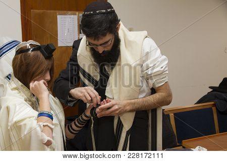 Tel Aviv, Israel - 19 January 2018: An Orthodox Man, Wearing Prayer Shawl, Put A Jewish Tefillin On