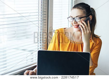 Business Woman In Orange Shirt Smiling Talking At Phone Near The Table And Looking At Laptop