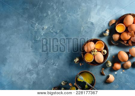 Header With Raw Brown Hen And Quail Eggs, Whole And Broken, On Two Wooden Dishes. Concrete Backgroun