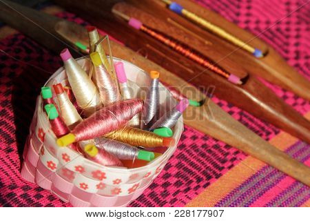 Colorful Bobbins In Basket And Wooden Bobbin On Silk Fabric