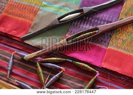 Colorful Bobbins And Wooden Bobbin On Silk Fabric
