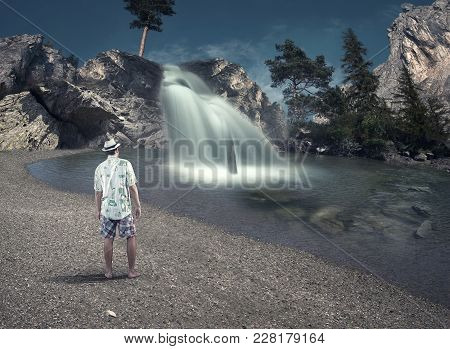 Young Looking Towards A Waterfall Near The Lake.