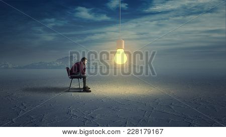 Thoughtful Man In Wilderness Looks To A Yellow Light Bulb Coming Down From The Sky.