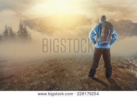 Young Hiker On The Mountains At Sunrise On A Foggy Day.