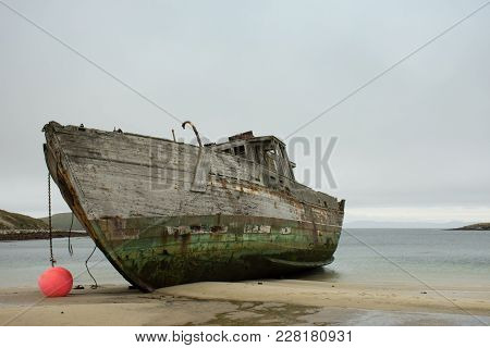 Close Up Of An Old Wooden Shipwrecked Boat Run Aground On A Tan Sandy Beach On New Island In The Fal
