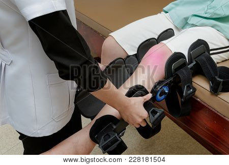 Physiotherapist Fixing Knee Braces On Patient's Leg In Hospital