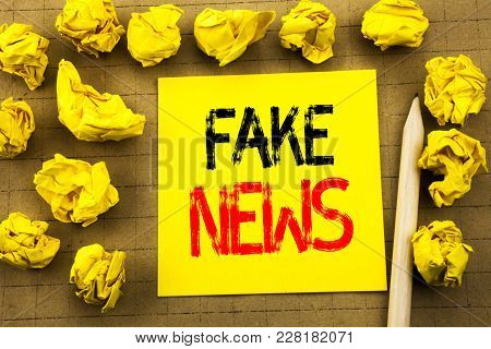 Fake News. Business Concept For Hoax Journalism Written On Sticky Note Paper On Vintage Background.