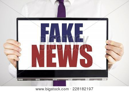 Word, Writing Fake News. Business Concept For Hoax Journalism Written On Tablet Laptop Holding By Ma