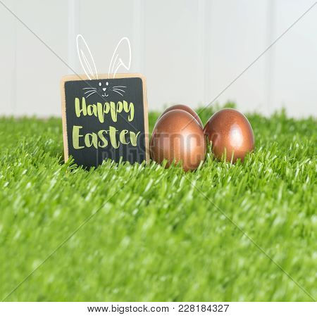 Happy Easter With Doodle Rabbit On Blackboard And Rose Gold Color Easter Eggs On Green Grass Field A