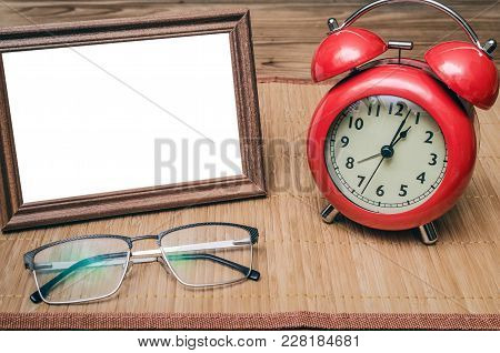 Blank Empty Photo Frame With Copy Space And Retro Style Red Alarm Clock And Glasses On Wooden Office