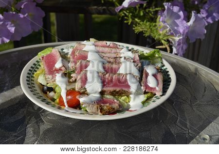 Ahi Tuna Sliced And Placed On A Summer Salad On The Outdoor Patio Table