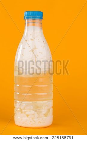 Sour Milk In A Plastic Bottle. Located On The Orange Background.