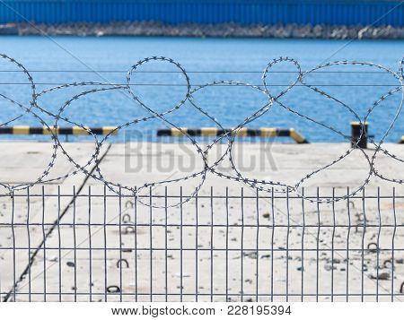 Metal Fence From The Mesh-rabittsi And Barbed Wire On The Background Of A Concrete Pier With A Fence