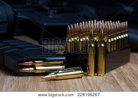 .223 Caliber Ammunition, Standing In Its Packaging, With Loose Bullets And A Full Magazine In The Fo