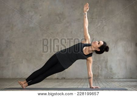 Young Woman Practicing Yoga, Doing Vasisthasana Exercise, Side Plank Pose, Working Out, Wearing Spor