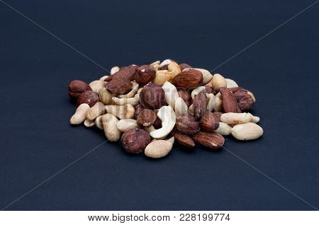 Variety Of Nuts Isolated On A Black Background. Front View Of 45 Degrees.
