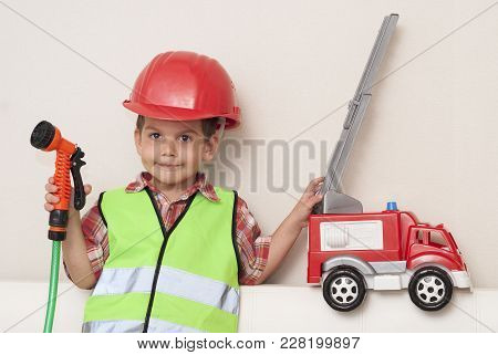 Child In A Red Helmet And With A Fire Engine